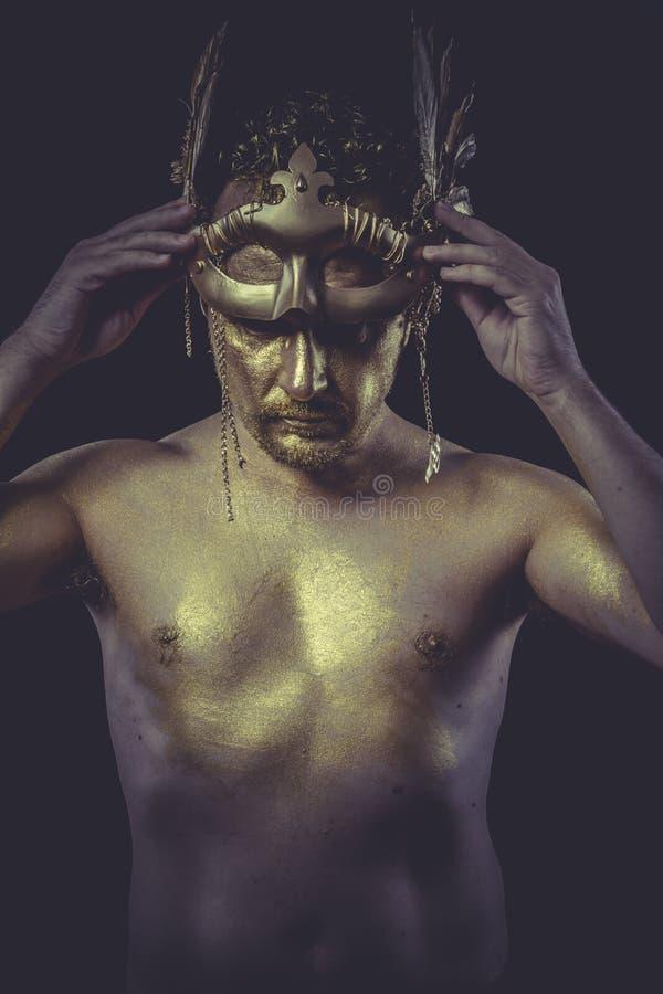 D'or, l'homme avec le corps a peint le masque de plume d'or et l'épée d'acier images stock