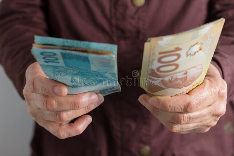 D?lares canadenses e moeda brasileira Ideia dianteira da m?o do ` s da mulher adulta que segura contas fotografia de stock