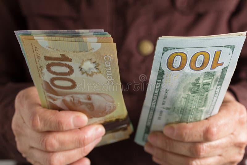 D?lares canadienses y moneda norteamericana Persona mayor de la vista delantera que lleva a cabo cuentas fotografía de archivo