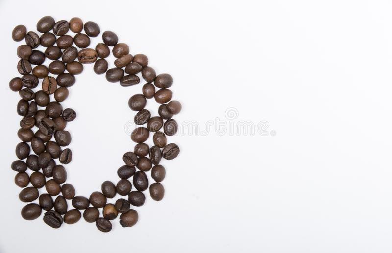D - large letter of english alphabet. Made up of unmolished roasted coffee beans on a white background stock photos