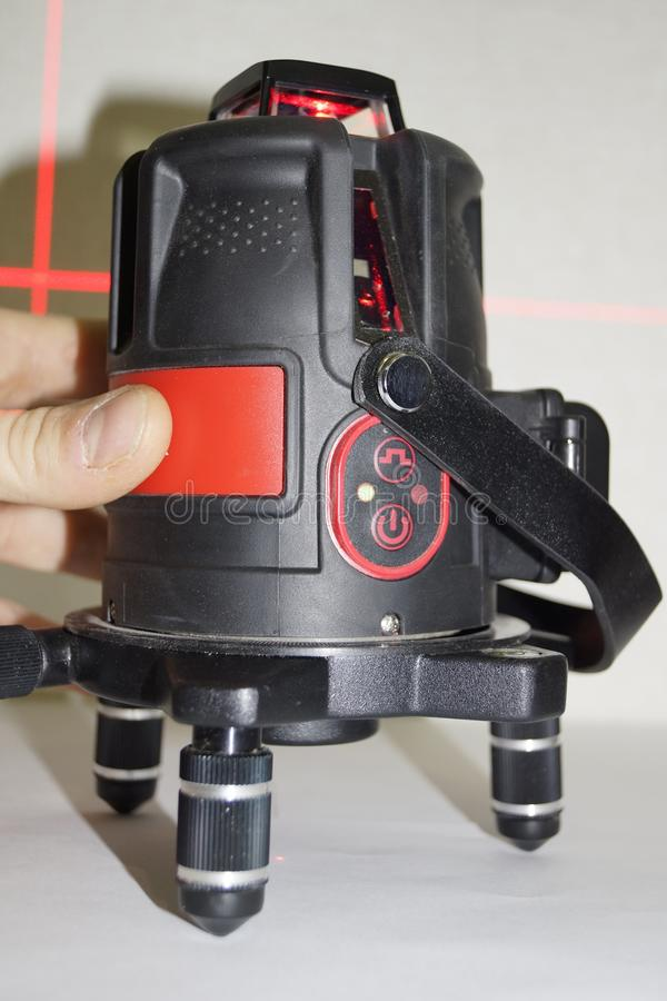 Laser level. 3D laser level with a reflected red beam on the wall stock photography