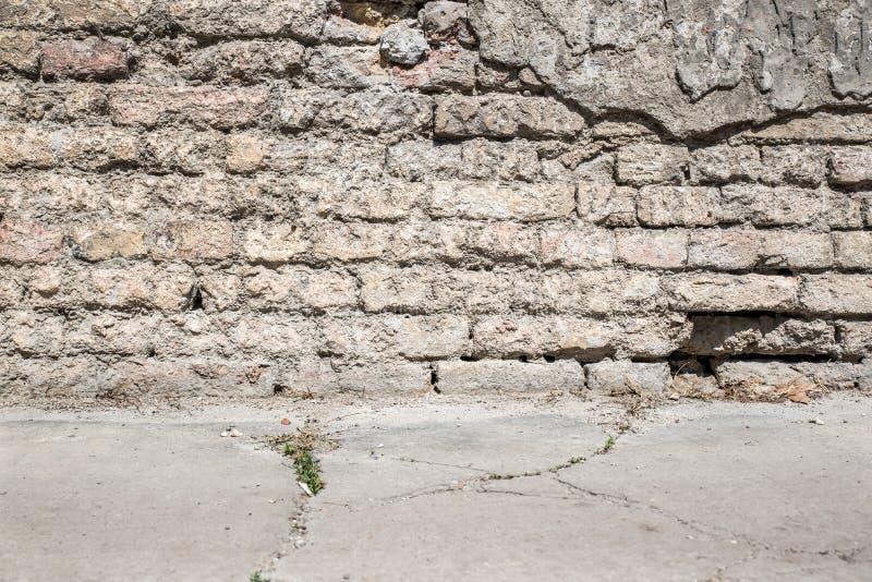 D?lig fundamentgrund p? gammalt hus eller byggnad kn?ckt murbrukfasadv?gg med tegelstenbakgrund arkivfoto