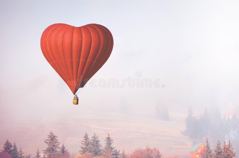 D luchtballon in de vorm van een hart die in mistig bos vliegen royalty-vrije stock fotografie