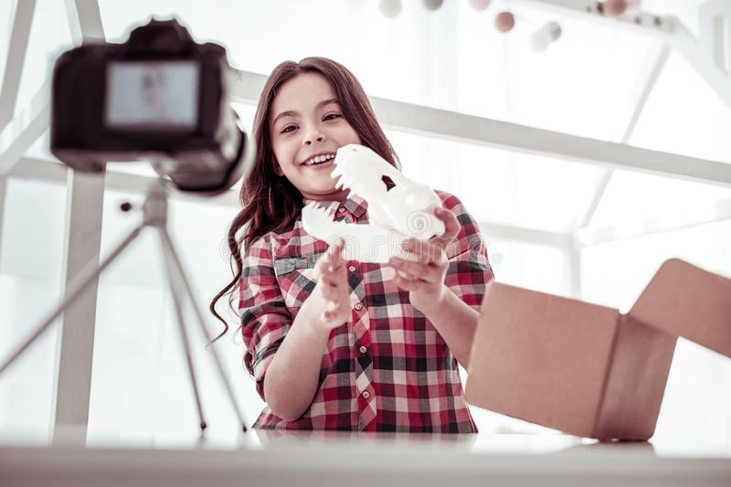 Delighted nice girl playing with a dinosaur model. 3d modeling. Delighted nice girl standing in front of the camera while playing with a dinosaur model royalty free stock image