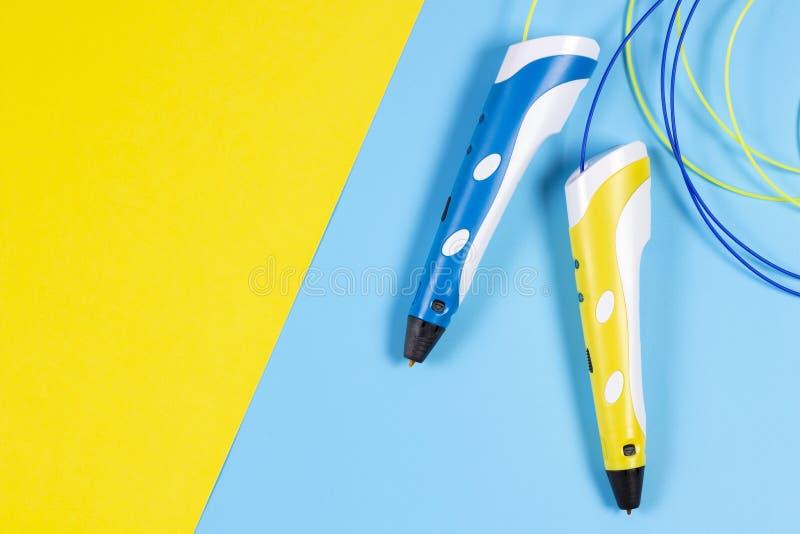 3d pennen met kleurrijke plastic gloeidraad op blauwe en gele achtergrond stock fotografie