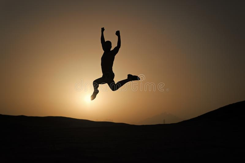 D?placement Keep Saut de mouvement d'homme de silhouette devant le fond de ciel de coucher du soleil Motivation quotidienne Mode  images libres de droits