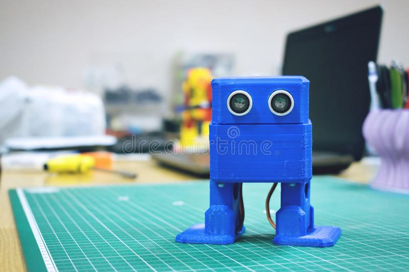 3D printed Funny dancing blue robot on the background of devices and laptop. Robot model printed on automatic three dimensional 3d. Printer. Additive royalty free stock photos