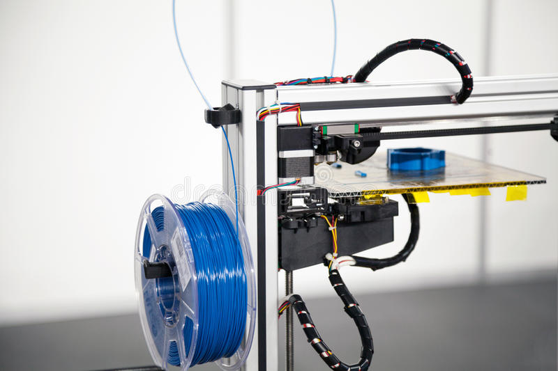 3d printer with blue filament coil close-up. 3d printing process stock photography