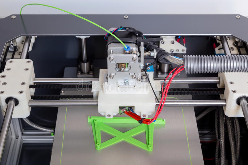 3d printer with bright green filament.  stock photography