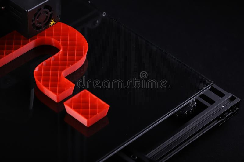 A 3D-printer manufacturing a big question mark from red plastic in dark surrounding with classy light mood. royalty free stock image