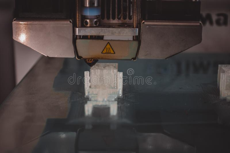 3D printer working and creating an object from the hot molten plastic close-up. Copy space. stock images