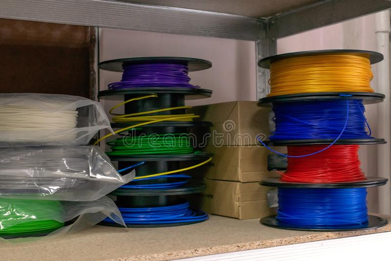 3D printing material, ABS filament, PLA & x28;Polylactic Acid& x29;,  PVA Filament.  Colored polymer in coils on the shelves stock image