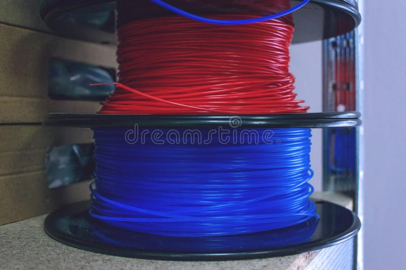 3D printing material, ABS filament, PLA & x28;Polylactic Acid& x29;,  PVA Filament.  Colored polymer in coils on the shelves royalty free stock photo