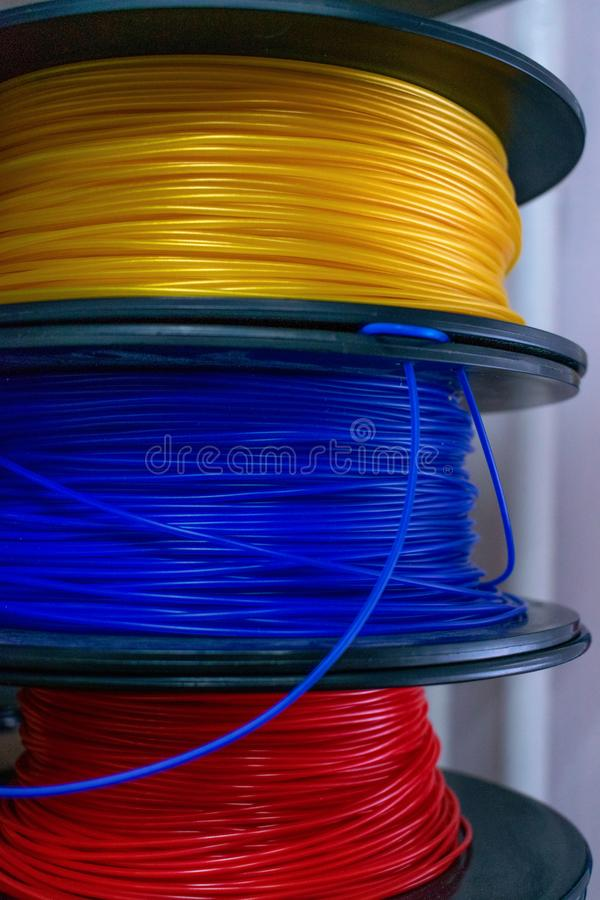 3D printing material, ABS filament, PLA & x28;Polylactic Acid& x29;,  PVA Filament.  Colored polymer in coils on the shelves stock photo
