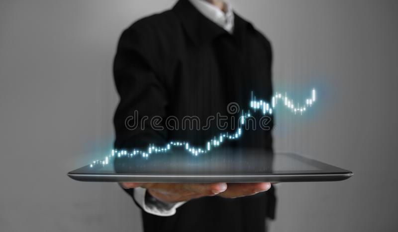 3D rendering of annual business performance report stock candle stick charts glowing hologram hover over tablet. In a palm of business man. Concept of virtual royalty free stock photo