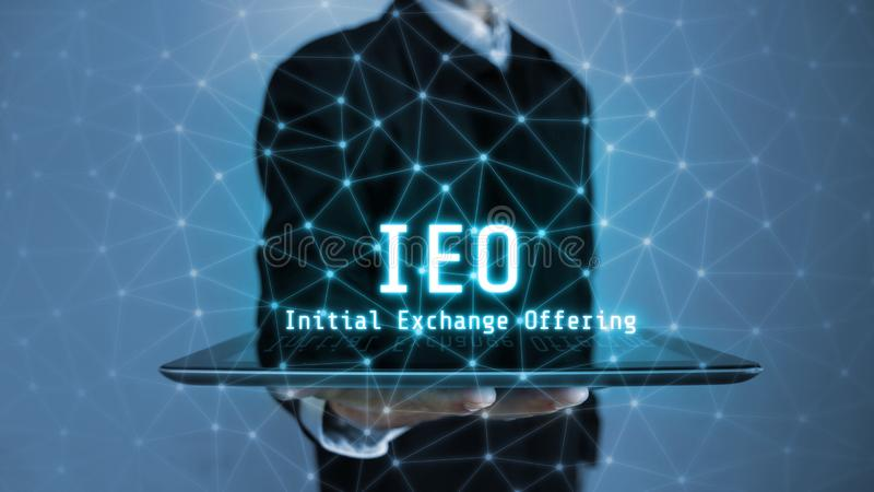3D rendering of IEO text Initial Exchange Offering glowing hologram hover over tablet in a palm of business man. royalty free stock images