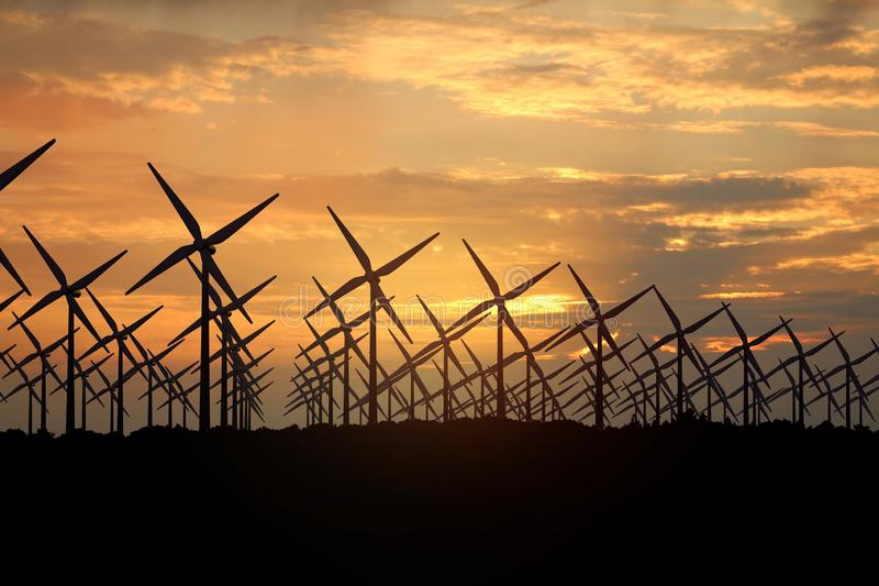 3D rendering of windmills producing engergy in the evening. 3D rendering of windmills in the sunset sky. Durable energy concept royalty free stock images