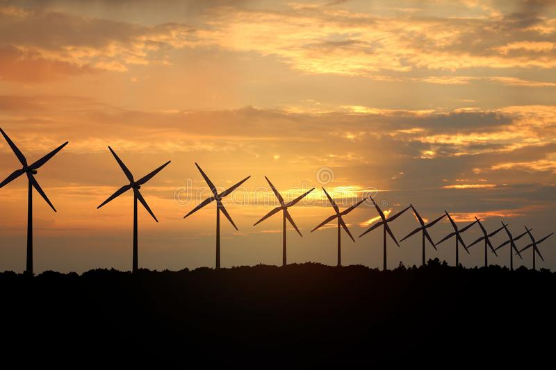 3D rendering of windmills producing engergy in the evening. 3D rendering of windmills in the sunset sky. Durable energy concept stock photos