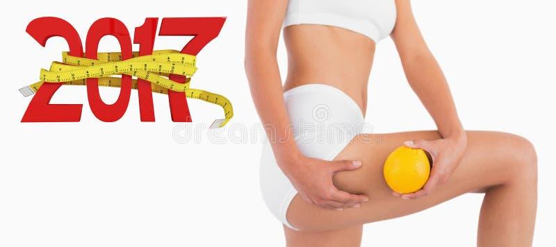 3D Samengesteld beeld van slanke vrouwelijke lichaamsholding sinaasappel en het drukken van haar dij royalty-vrije stock afbeeldingen