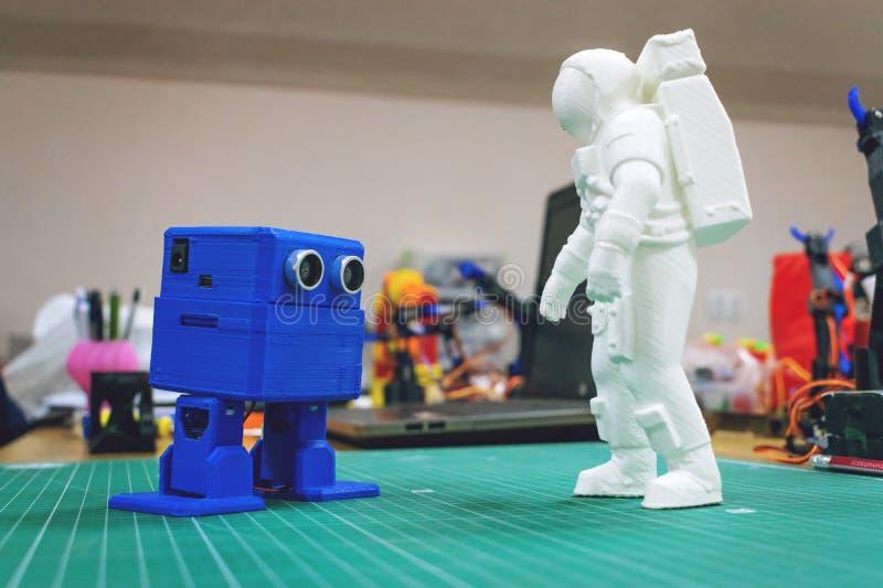 3D skrivev ut astronautet, kosmonautet och den gulliga roboten på bakgrunden av apparater och bärbara datorn royaltyfri fotografi