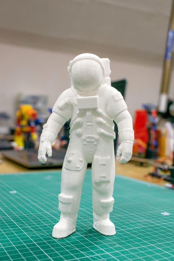 3D skrivev ut astronautet, kosmonautet, roboten på bakgrunden av apparater och bärbara datorn Astronautmodell som skrivs ut på au royaltyfri fotografi