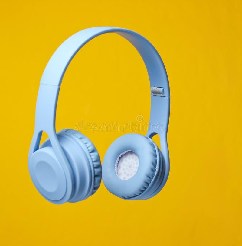 3D surround photo blue wireless headphones. On yellow background stock photography