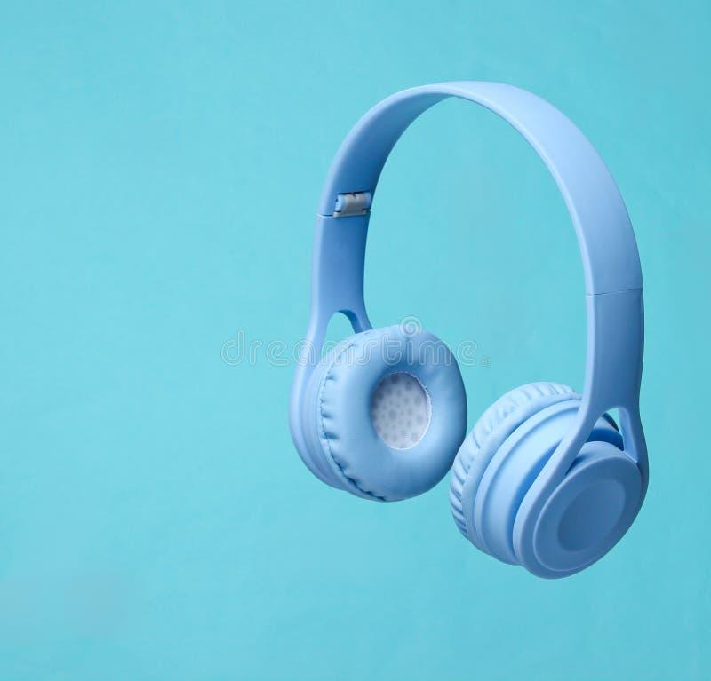 3D surround photo modern wireless blue headphones on blue background. 3D surround photo modern wireless blue headphones on blue background stock photography