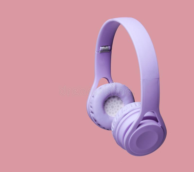 3D surround photo purple wireless headphones. On coral color background stock image