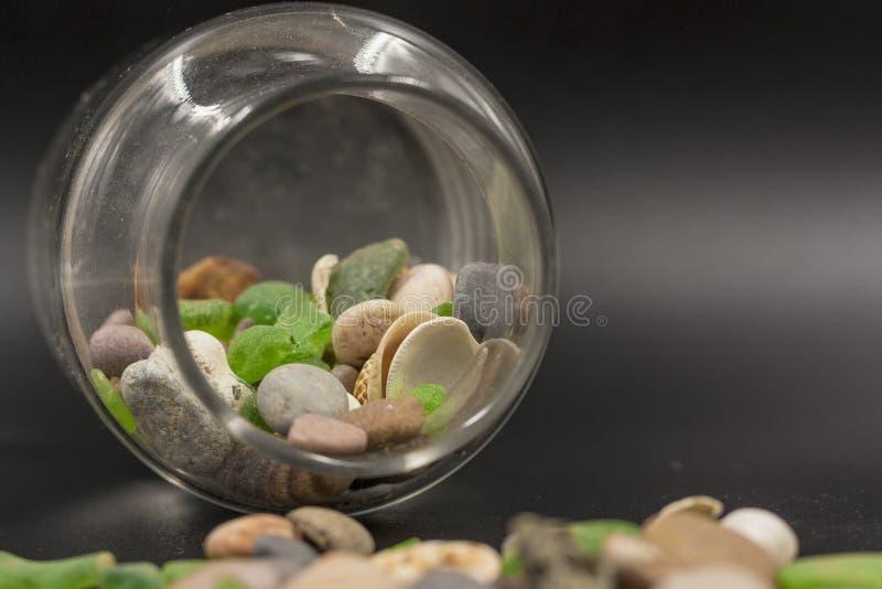 D?tail de la bouteille en verre avec des pierres ? l'int?rieur et dispers? sur le plancher photo stock