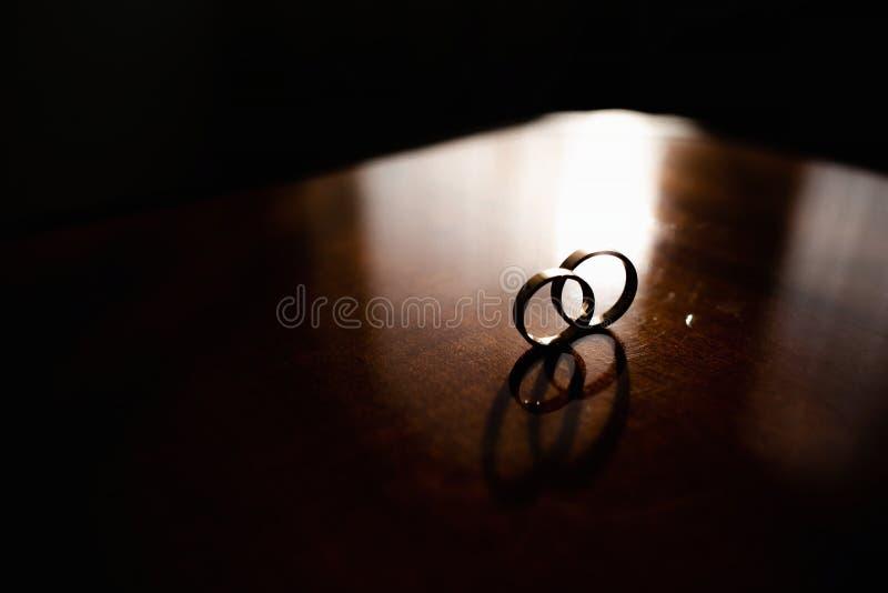 D?tails du matin du jour du mariage deux anneaux de mariage d'or sont sur la table en bois brune images libres de droits