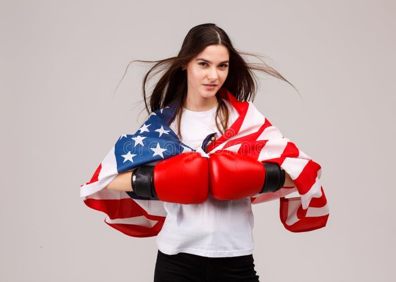 D'une jeune des positions fille dans des gants de boxe et est couvertes de drapeau américain sur ses épaules photographie stock