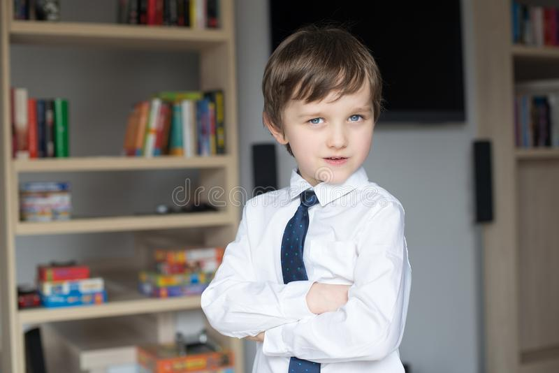 D'une manière élégante habillé dans une chemise blanche et garçon de lien un petit image libre de droits