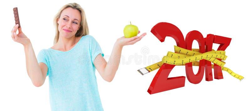 3D Złożony wizerunek trzyma baru czekolada i jabłko uśmiechnięta blondynka fotografia stock