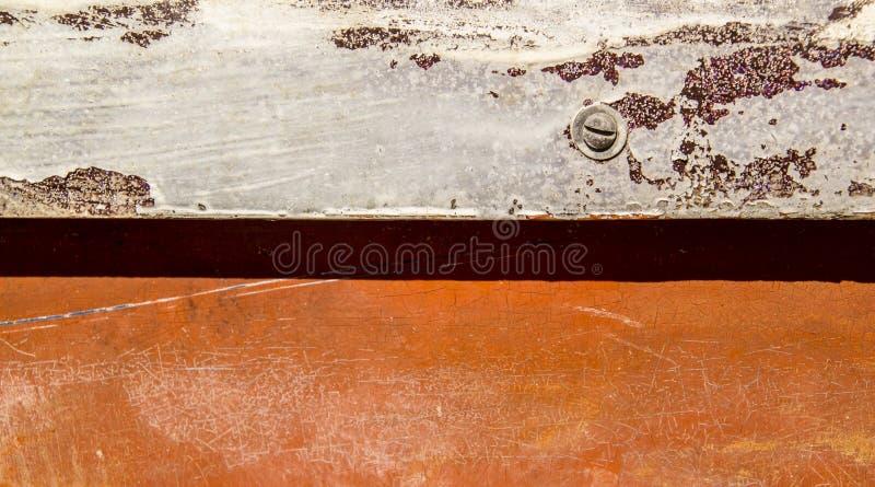 Dañado pintado vieja superficie anaranjada y blanca con el tornillo imagen de archivo libre de regalías