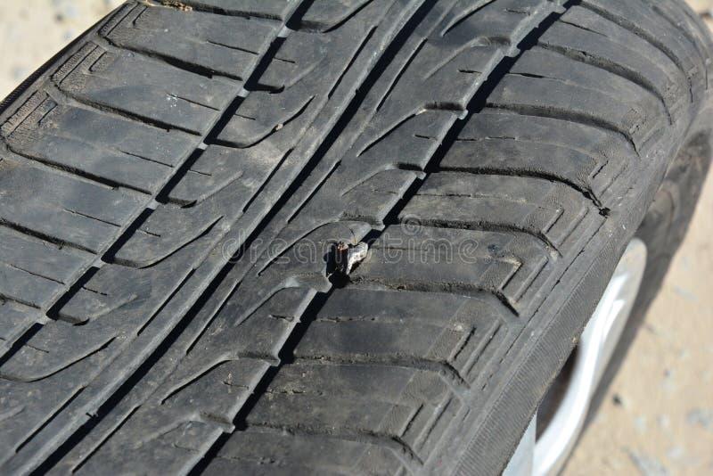 Daño del neumático de coche con el clavo Neumático de coche plano fotos de archivo libres de regalías
