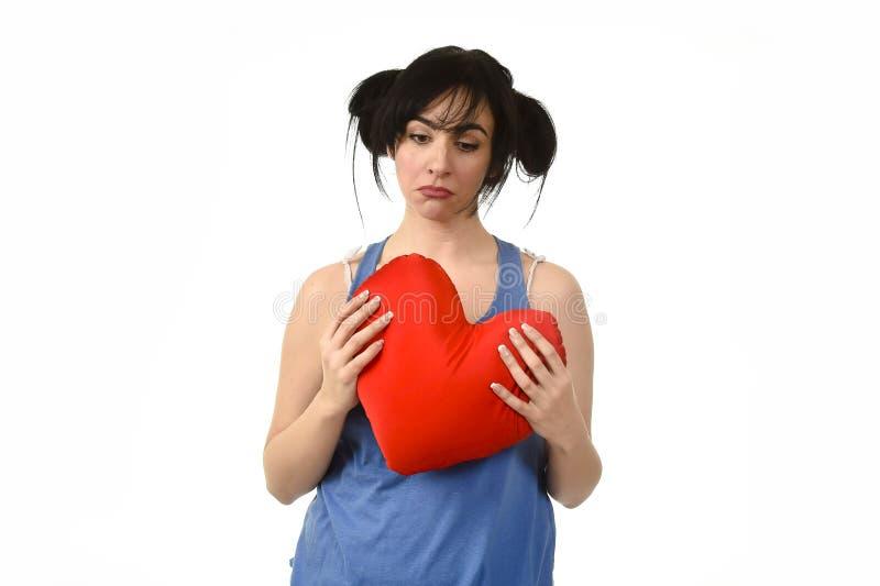 Daño hermoso de la mujer y sufrimiento para el amor perdido que sostiene la almohada roja de la forma del corazón imagen de archivo