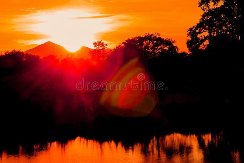 Da árvore colorida bonita da silhueta da paisagem do por do sol e da luz favoravelmente rio reflexo da água no tempo do crepúscul fotografia de stock royalty free