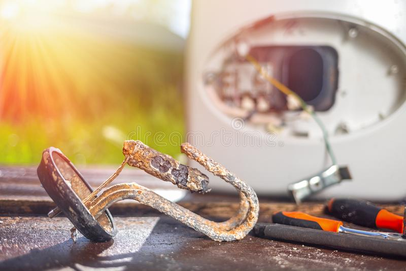 Da?ado de la corrosi?n y del moho, el calentador de agua miente con los instrumentos en el fondo de la caldera en una tabla de ma imagen de archivo