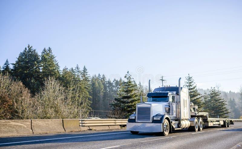 Da capota do ídolo americano do equipamento caminhão grande poderoso semi com semi o reboque abaixador que move-se na estrada lar imagem de stock