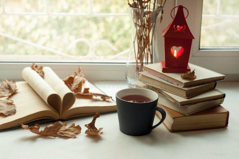 Da casa vida acolhedor ainda: castiçal e livros na soleira contra a paisagem fora Feriados do outono, lendo o conceito do tempo imagens de stock