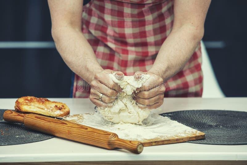 Da el primer de un cocinero que haga la pasta en la cocina fotos de archivo