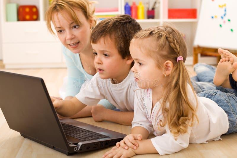 Da família miúdos em linha - que aprendem o uso dos computadores fotos de stock royalty free