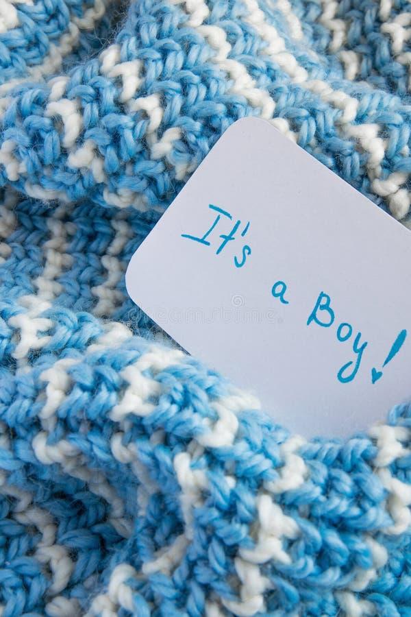 ` Da festa do bebê ele ` s um ` do menino, cartão do anúncio na cobertura azul de lã acolhedor e espaço para o texto Chegada nova foto de stock