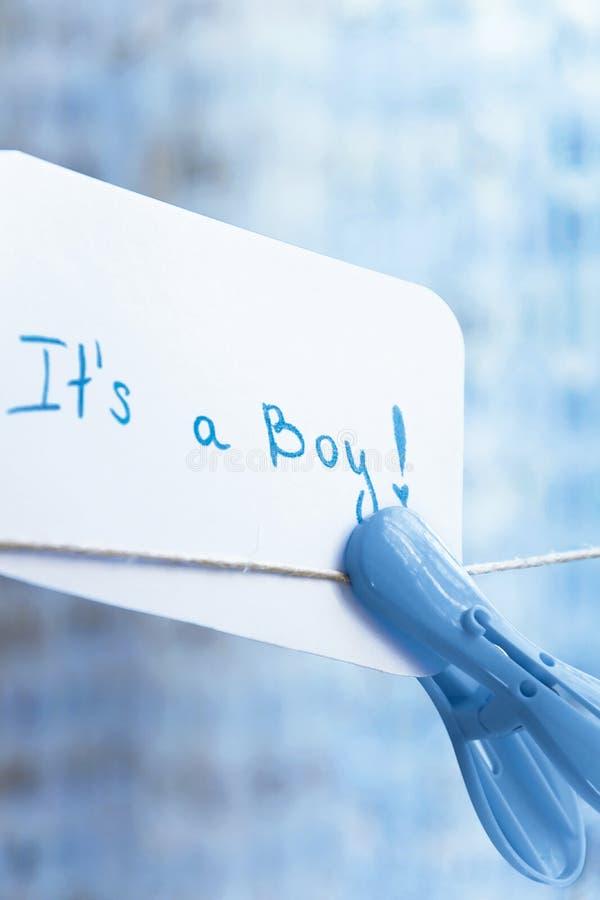 ` Da festa do bebê ele ` s um ` do menino Cartão simples da celebração que pendura no fio com pregador de roupa azul e no espaço  fotos de stock