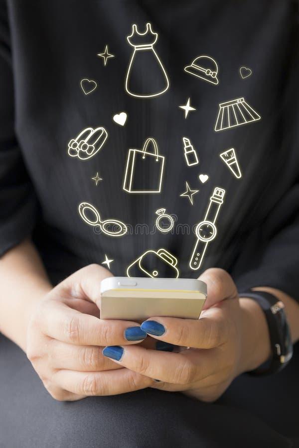 Da la mujer que sostiene el teléfono elegante con la línea iconos de la ropa stock de ilustración