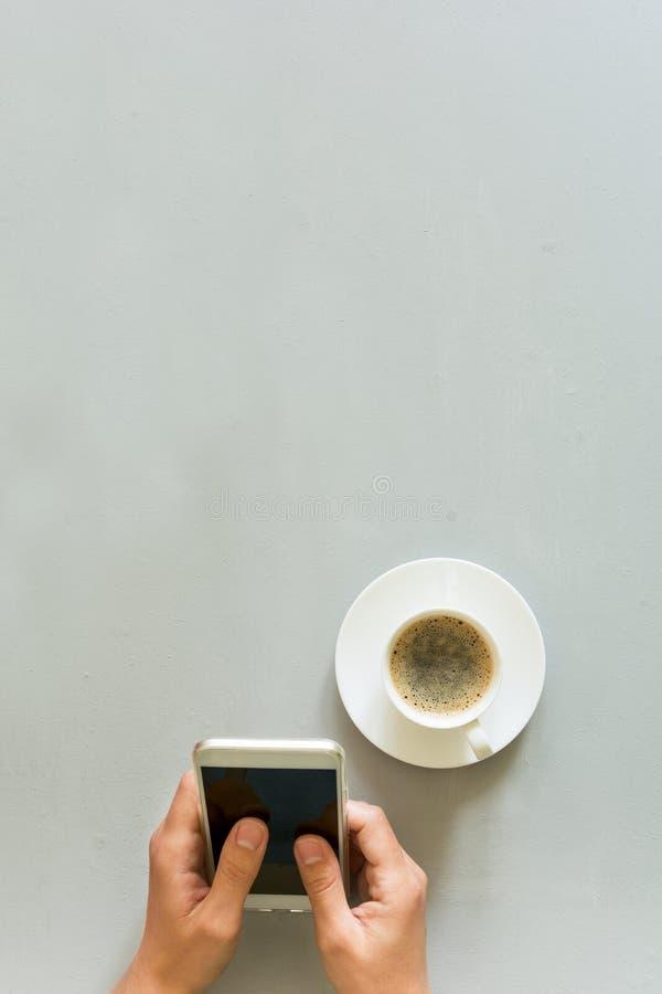 Da la mujer que usa el teléfono elegante en la tabla de madera gris Tiempo del café Ritual de la mañana imagenes de archivo