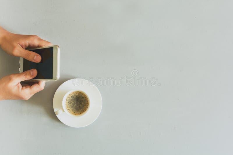 Da la mujer que usa el teléfono elegante en la tabla de madera gris Tiempo del café Ritual de la mañana imagen de archivo