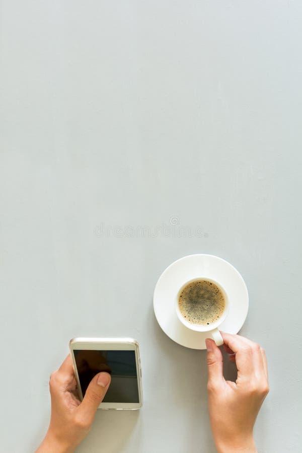 Da la mujer que usa el teléfono elegante en la tabla de madera gris Tiempo del café Ritual de la mañana fotografía de archivo libre de regalías