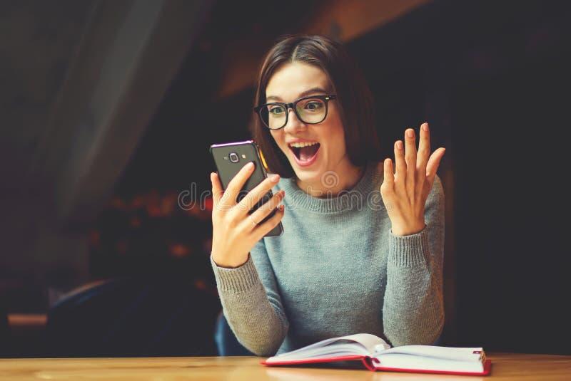 Da leitura fêmea dentro surpreendida e entusiasmado livro interessante após o trabalho foto de stock