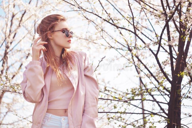 Da mola da forma da menina retrato fora em árvores de florescência Mulher romântica da beleza nas flores nos óculos de sol Senhor imagem de stock royalty free